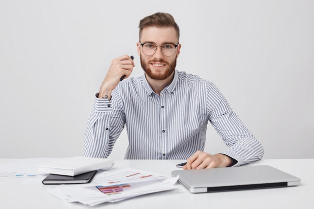 Hombre emprendedor ocupado trabaja con papeles o documentos en la oficina, sostiene la pluma