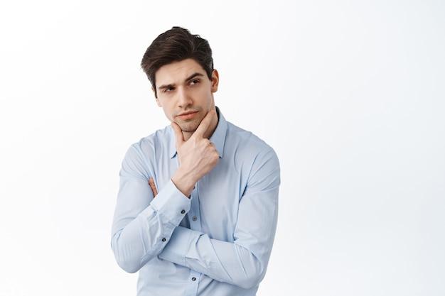 Hombre emprendedor reflexivo, director ejecutivo pensando, mirando a un lado la promoción y haciendo una elección, de pie contra la pared blanca