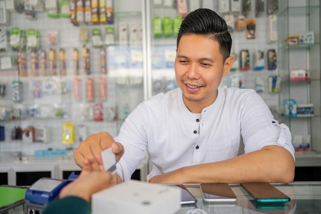 Un hombre emprendedor sentado detrás de una vitrina que sirve a un comprador de teléfonos móviles