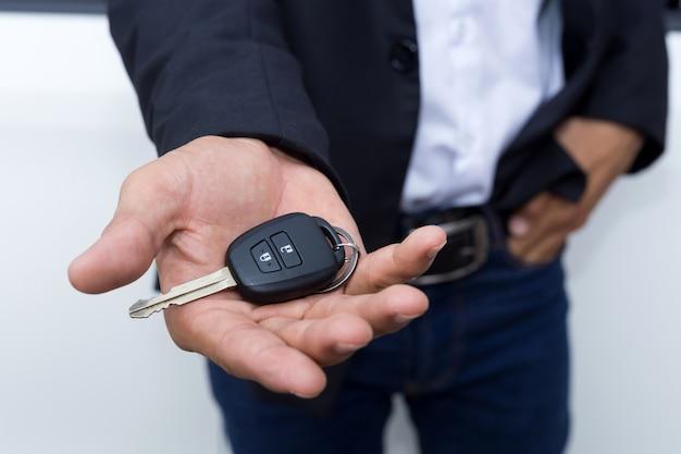 Hombre empresario adulto en un traje y sosteniendo una llave del coche en la mano. autos blancos en el fondo