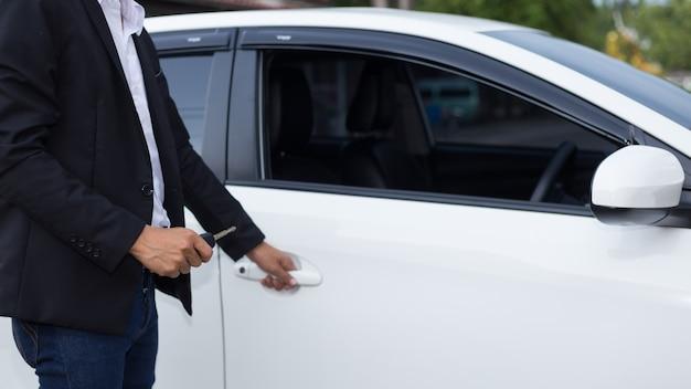 Hombre empresario adulto en un traje y sosteniendo una llave del coche en la mano