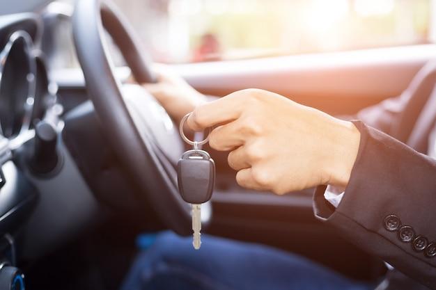 Hombre empresario adulto en un traje y sosteniendo una llave de coche en su mano