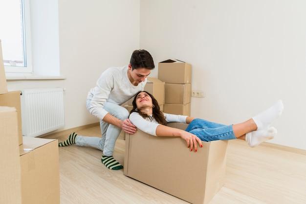 Hombre empujando a la joven excitada sentada dentro de la caja de cartón