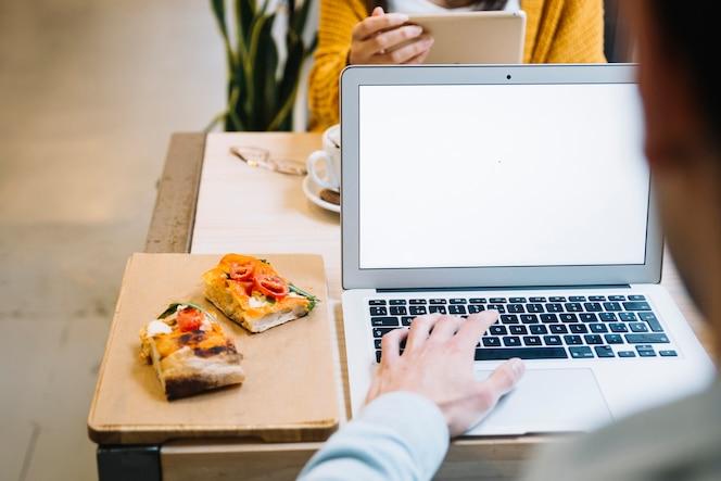 Hombre en el restaurante concentrándose en la computadora portátil