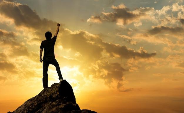 Hombre en la cima de la montaña y la luz del sol, éxito, concepto de ganador