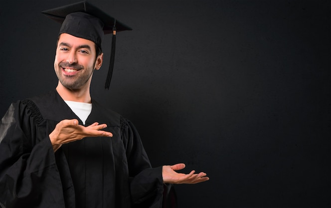 Hombre en su día de graduación universidad extendiendo las manos hacia un lado y sonriendo para presentin