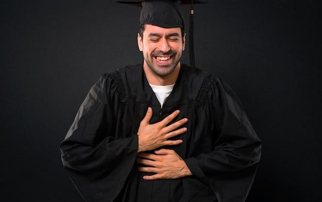 Hombre en su día de graduación universidad sonriendo mucho mientras pone las manos en el pecho sobre fondo negro