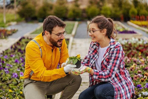 Hombre enamorado dando maceta con flores a su novia