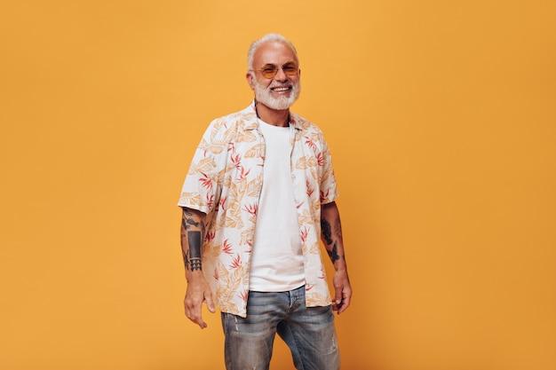 Hombre encantador en jeans, camisa y gafas de sol posa en la pared naranja