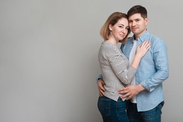 Hombre encantador y mujer abrazados mientras posan