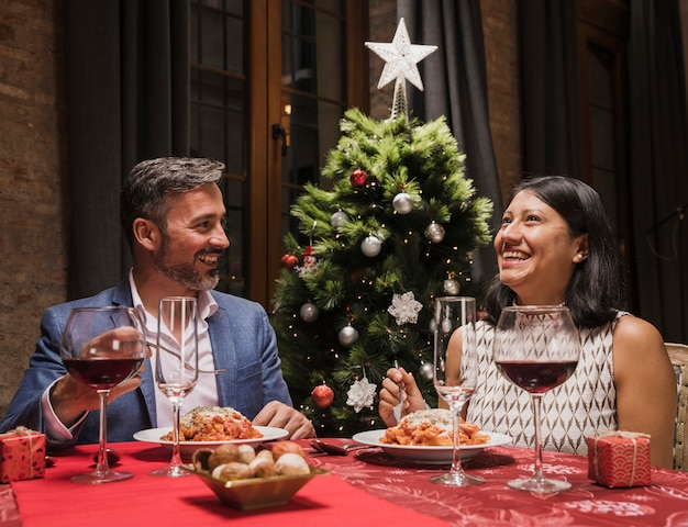 Hombre encantador y mujer en la cena de navidad