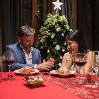 Hombre encantador y mujer cenando en navidad