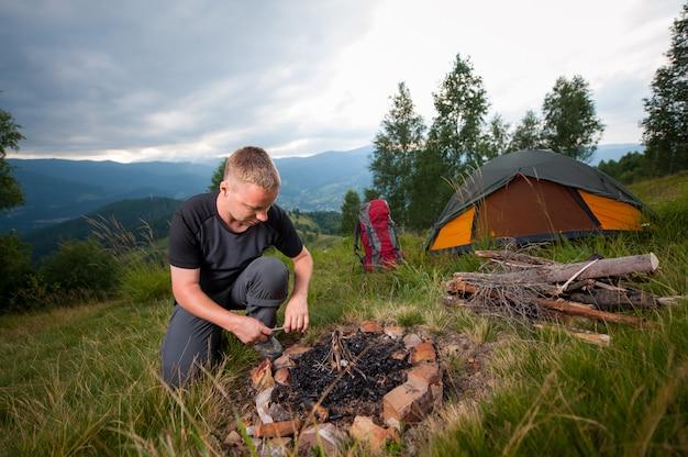 Hombre encendiendo leña en la colina