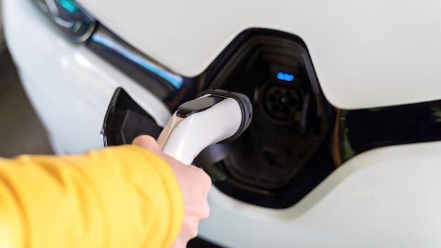 Hombre enchufar el cargador en un coche eléctrico blanco
