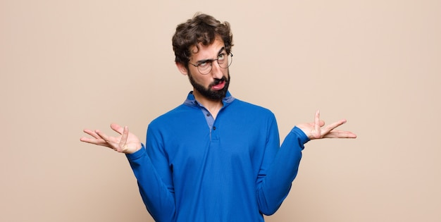 Hombre encogiéndose de hombros hombre con una expresión tonta, loca, confundida, perpleja, sintiéndose molesto y despistado