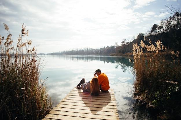 El hombre se encuentra en la orilla del lago de garda contra el cielo del atardecer