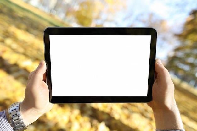 El hombre se encuentra en el parque otoño y mira tablet