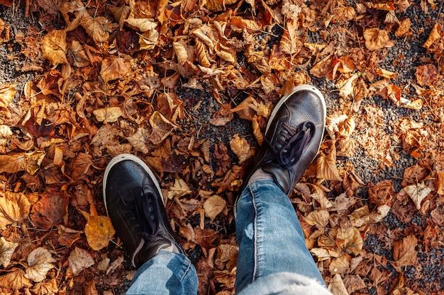 El hombre se encuentra en zapatillas de deporte en el parque de otoño