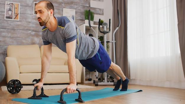 Hombre enérgico haciendo ejercicios de pecho en estera de yoga en casa.