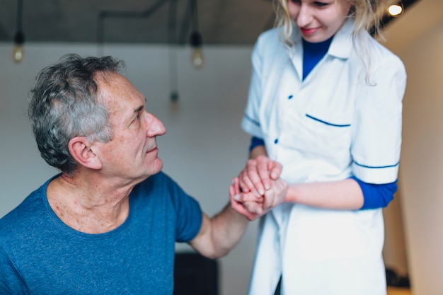Hombre y enfermera cogiéndose las manos en asilo de ancianos