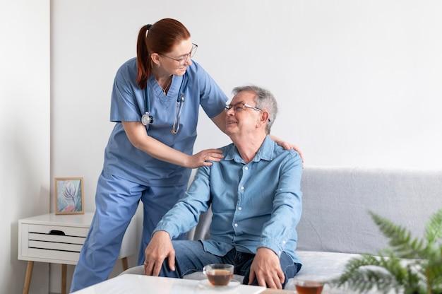 Hombre y enfermera sonriente de tiro medio