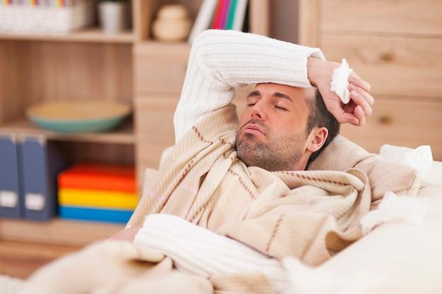 Hombre enfermo acostado en el sofá con fiebre alta