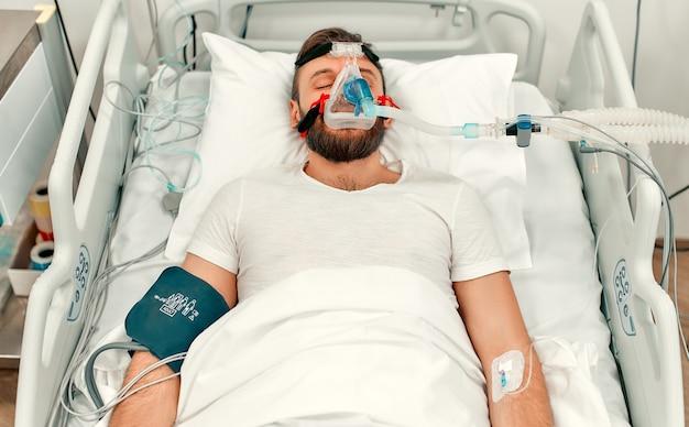 Hombre enfermo adulto yace en una cama en una unidad de cuidados intensivos