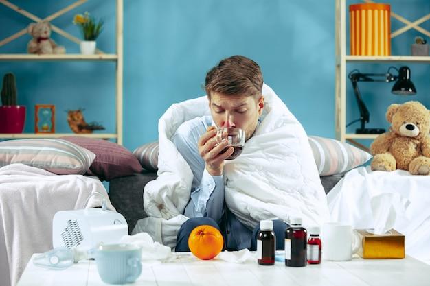 Hombre enfermo barbudo con chimenea sentado en el sofá en casa cubierto con una manta caliente y bebiendo jarabe de tos. la enfermedad, la gripe, el concepto de dolor. relajación en casa