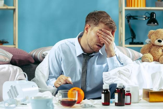 Hombre enfermo barbudo con chimenea sentado en el sofá en casa cubierto con una manta caliente y bebiendo jarabe de tos.