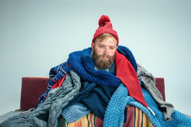 Hombre enfermo barbudo con chimenea sentado en el sofá en casa o estudio cubierto con ropa de abrigo tejida. enfermedad, concepto de influenza. relajación en casa. conceptos sanitarios.