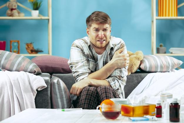 Hombre enfermo barbudo con chimenea sentado en el sofá en casa.