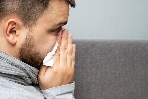 Un hombre está enfermo en casa con secreción nasal y gripe.