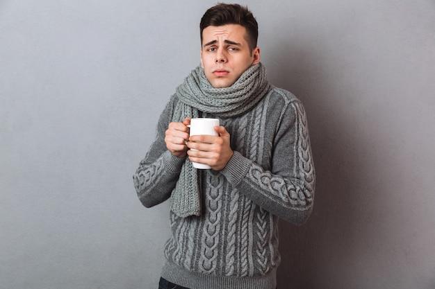 Hombre enfermo confundido en suéter y bufanda con servilleta y spray con dolor de cabeza