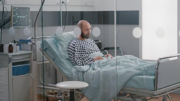 Hombre enfermo estresado sentado en la cama esperando tratamiento respiratorio