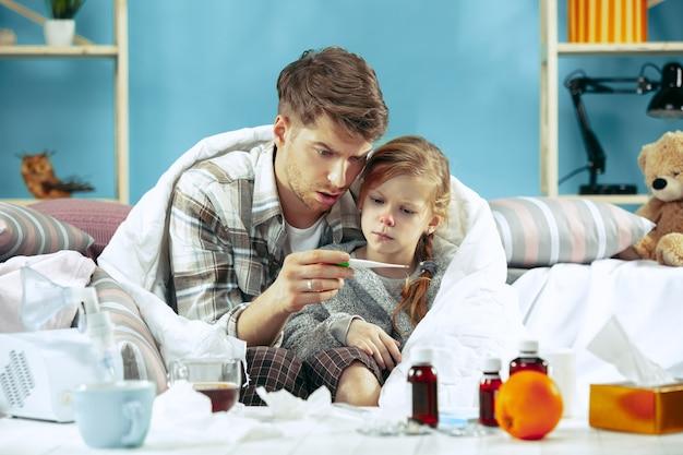 Hombre enfermo con hija en casa. tratamiento a domicilio. luchando con una enfermedad. asistencia médica. iilidad familiar. el invierno, la gripe, la salud, el dolor, la paternidad, el concepto de relación. relajación en casa