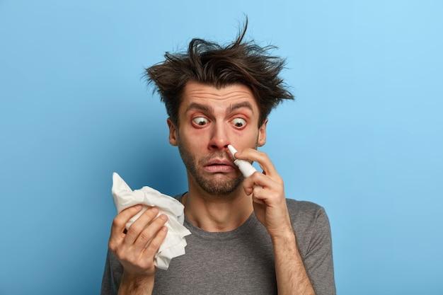 Un hombre enfermo se inyecta una gota nasal para la nariz tapada, sufre de resfriado, alergia o rinitis, se frota con un pañuelo, se siente mal, tiene ojos saltones, se aísla en la pared azul y permanece en casa durante el curso de la enfermedad