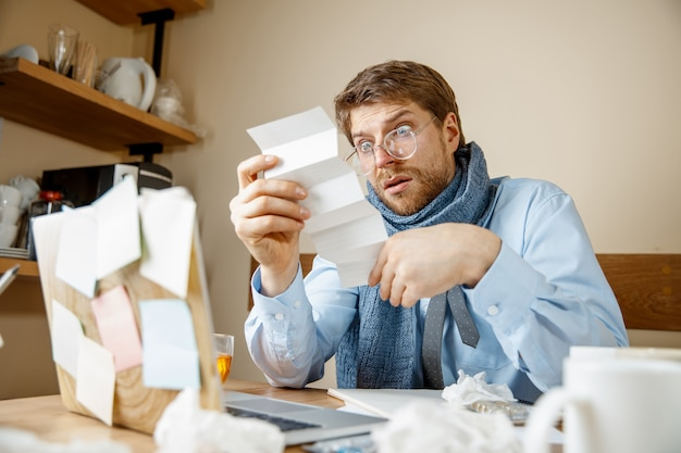 Hombre enfermo leyendo medicamentos recetados trabajando en office