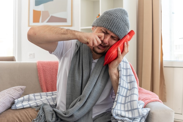 Hombre enfermo llorando con bufanda alrededor del cuello con sombrero de invierno sosteniendo y poniendo la cabeza en la bolsa de agua caliente sentado en el sofá en la sala de estar