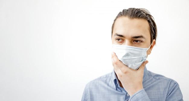 Hombre enfermo en la mascarilla quirúrgica tocando su rostro.