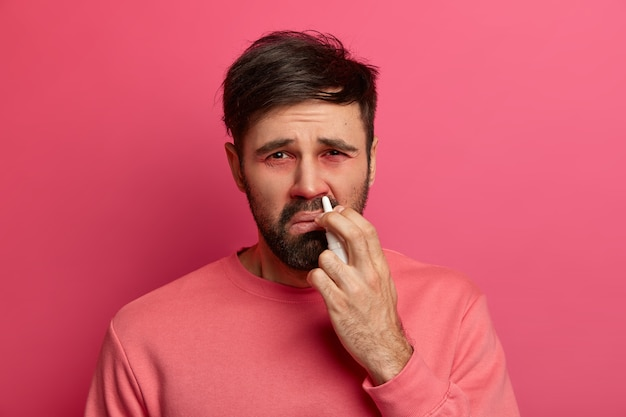 Un hombre enfermo molesto rocía medicamentos para la alergia en la nariz, se resfrió, sufre de rinitis, tiene los ojos enrojecidos e hinchados, está vestido con ropa casual, posa contra la pared rosada. concepto de tratamiento de enfermedades.