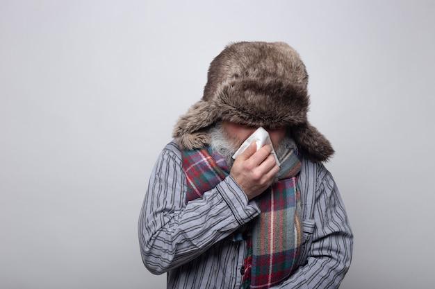 Hombre enfermo con pijama y gorra sonándose la nariz