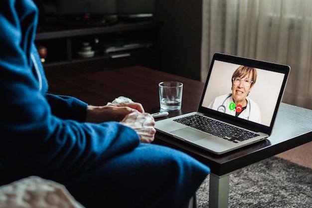 Hombre enfermo que tiene una consulta en línea con el médico en la computadora