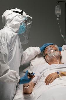 Hombre enfermo con respirador cogidos de la mano con un médico