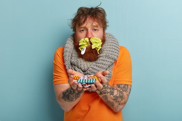 Hombre enfermo en ropa de abrigo con pañuelos de papel en la nariz y termómetro