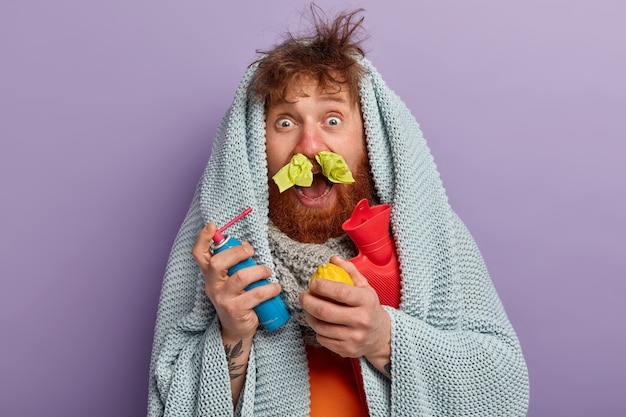 Hombre enfermo en ropa de abrigo con spray para nariz, limón y bolsa de agua