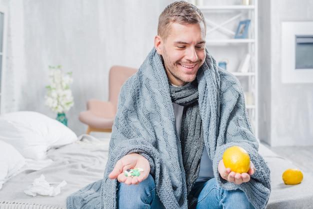 Hombre enfermo sonriente que se sienta en cama que se pregunta por el limón entero o las píldoras a disposición