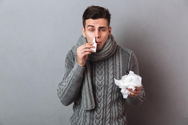 Hombre enfermo en suéter y bufanda sosteniendo servilleta y usando spray mientras mira