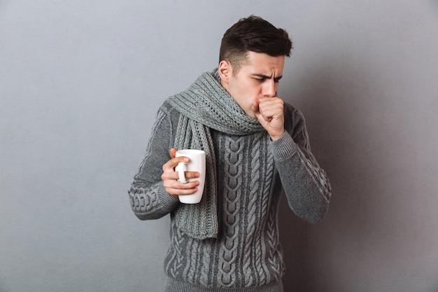 Hombre enfermo en suéter y bufanda sosteniendo una taza de té mientras tiene tos
