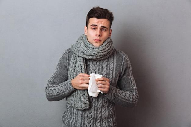 Hombre enfermo en suéter y bufanda sosteniendo una taza de té y mirando