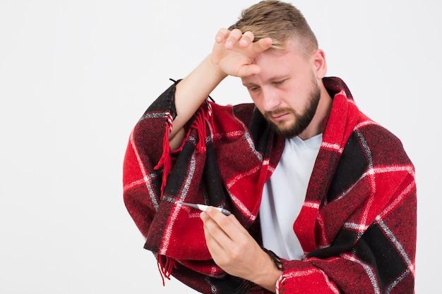 Hombre enfermo con termómetro